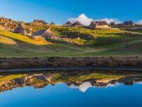 Velika planina shepherds' settlement reflected in a waterhole
